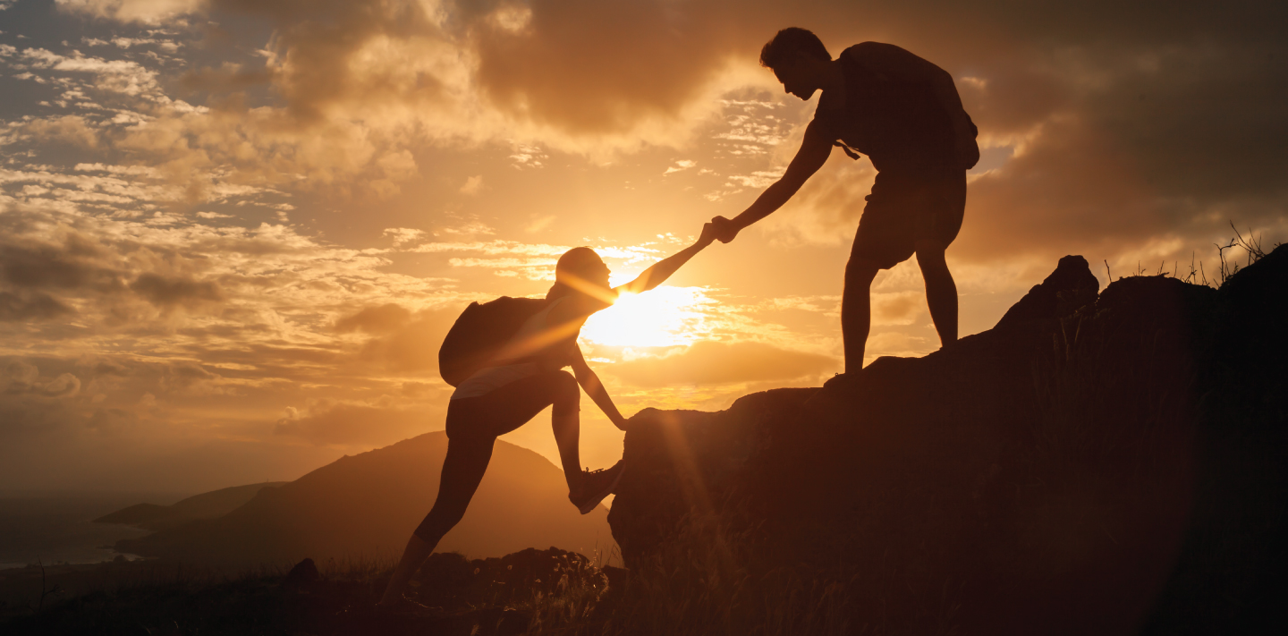 Man helping woman up rock on mountain at sunset